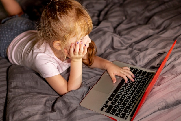 High angle girl on the laptop in the bedroom