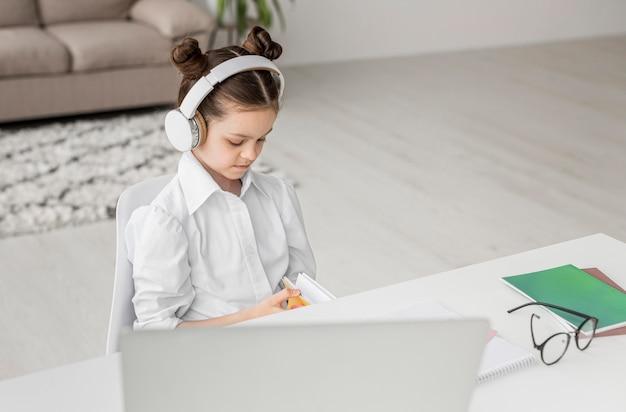 Девушка высокого угла слушая ее учителя через наушники