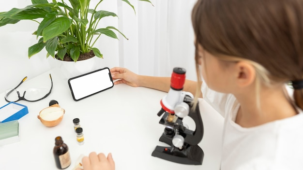 High angle of girl looking into microscope and holding smartphone
