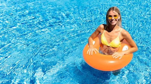 Высокий угол девушка позирует в бассейне
