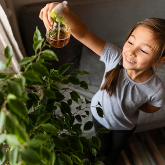 High angle of girl spraying plant with water