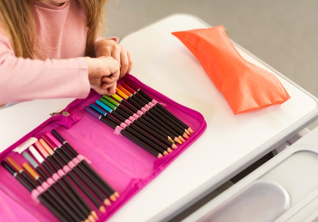 鉛筆ケースから鉛筆を取っているハイアングルの女の子