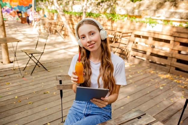 本とフレッシュジュースのボトルを持つハイアングルの女の子