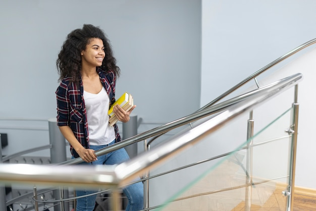 High angle girl with stack of books climbing stairs
