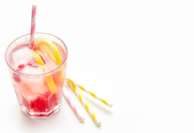 High angle glass of cranberry vodka with lemon and ice with copy-space