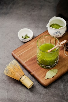 High angle of glass of matcha tea on chopping board