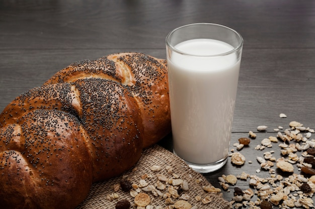 High angle glass of milk next to fresh bread