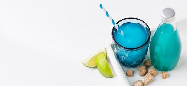 Alto angolo di bicchiere di bibita con calce e bottiglia