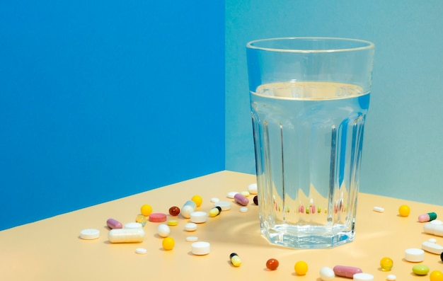 High angle of glass of water with pills surrounding it