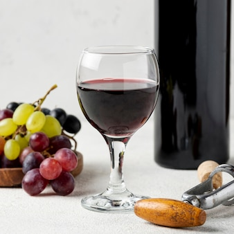High angle glass with red wine beside grapes