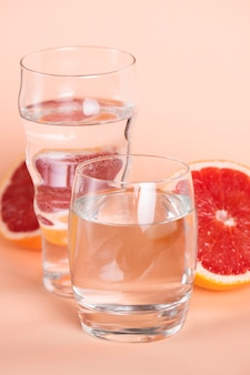 High angle glasses of water with red oranges