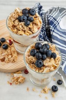 Alto angolo di bicchieri con cereali per la colazione e yogurt con frutta