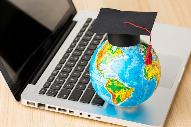 High angle of globe with academic cap and laptop