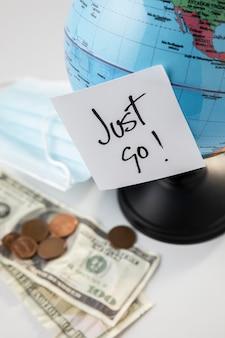 Alto angolo del globo con banconote e nota adesiva
