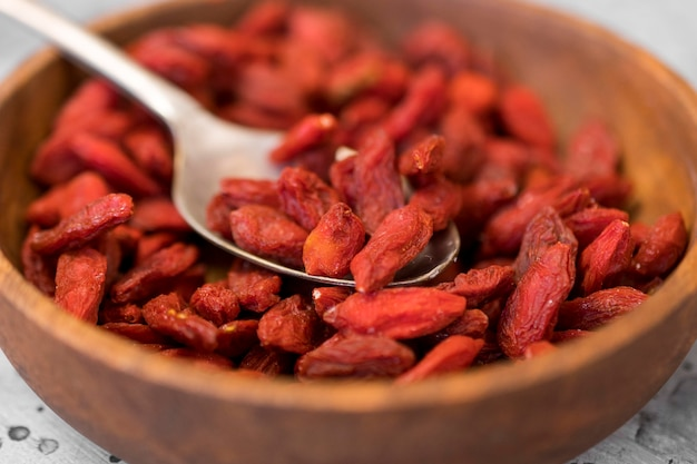 High angle of goji berries in bowl with spoon