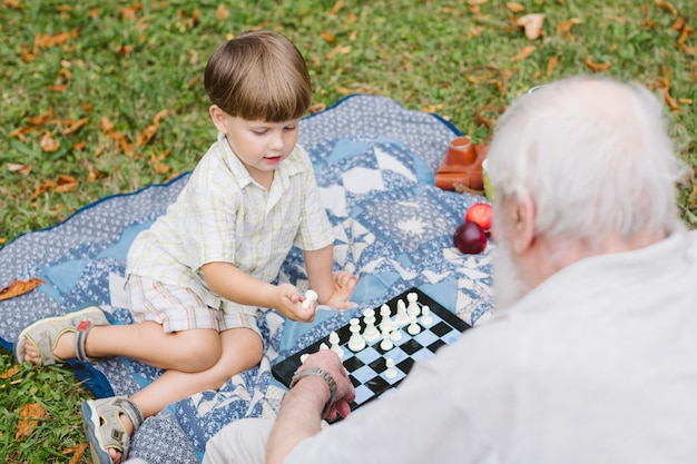 High angle grandpa and grandson playing chess