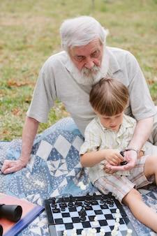 High angle grandpa teaching chess his grandson