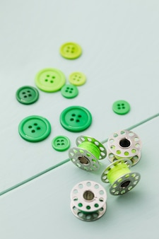 High angle of green buttons with sewing machine shuttles