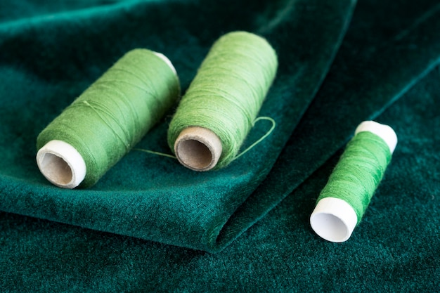 High angle of green thread rolls with velvet