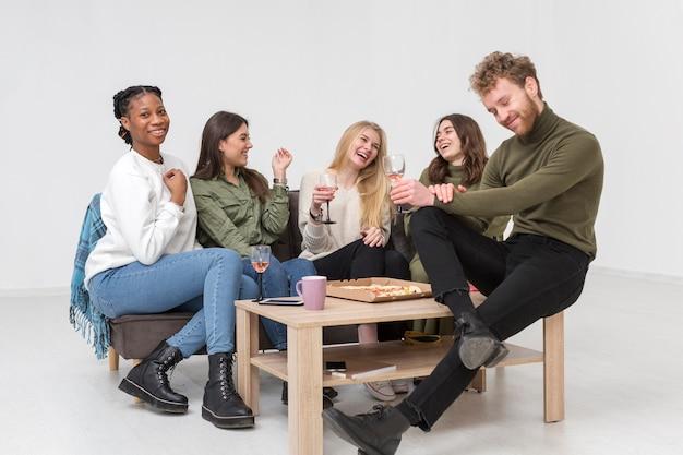 Высокий угол группы друзей, имеющих пиццу
