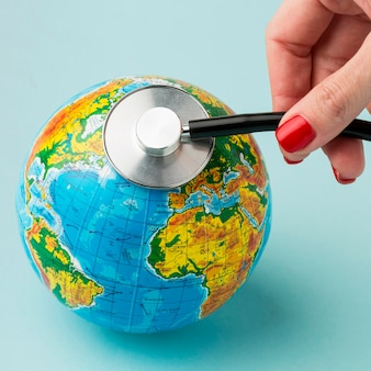 High angle of hand consulting earth with stethoscope