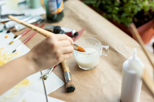 High angle hand holding painting brush