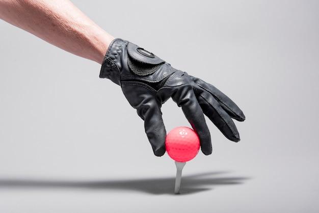High angle hand placing golf ball