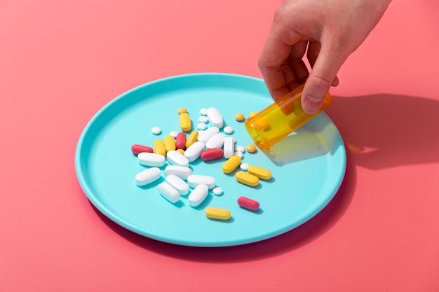 Pillole di versamento dell'angolo alto della mano sul vassoio dal contenitore