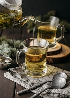 High angle hand pouring tea in glass with teapot