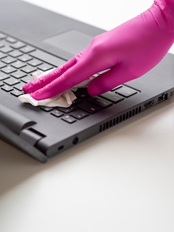 High angle of hand with surgical glove cleaning laptop