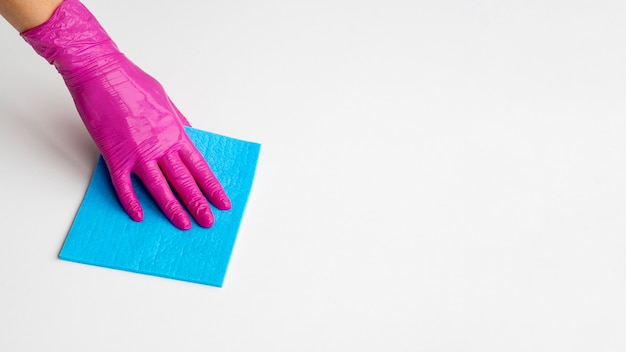 High angle of hand with surgical glove cleaning surface with copy space