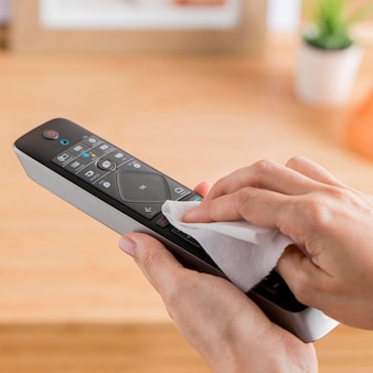 High angle of hands disinfecting remote controller