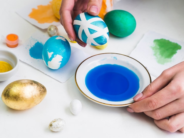 High angle of hands dyeing egg with design for easter