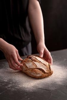 Mani dell'angolo alto che tengono pane