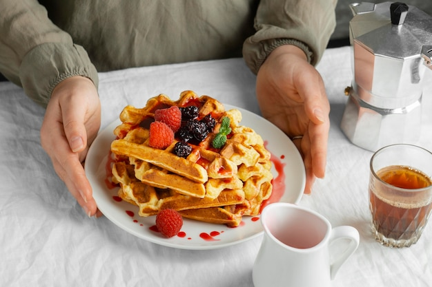 High angle hands holding plate with waffles