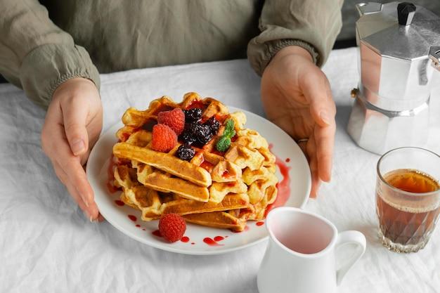 Руки под высоким углом держат тарелку с вафлями