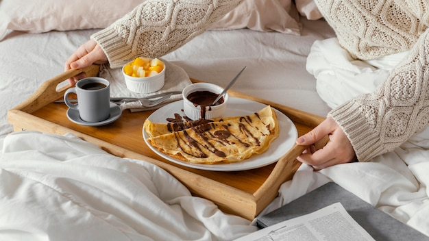 High angle hands holding tray with breakfast