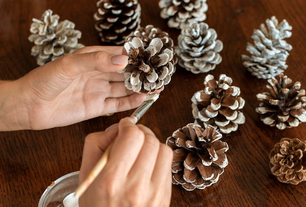 High angle of hands painting pine cones for christmas