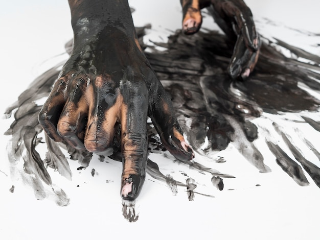 High angle of hands with black paint