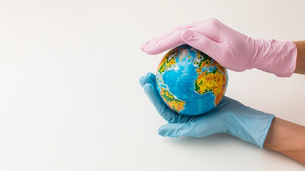 High angle of hands with gloves holding globe with copy space