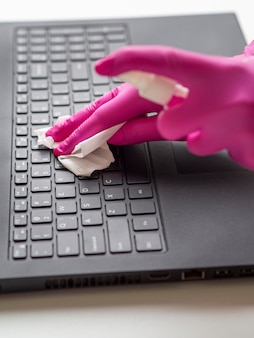High angle of hands with surgical gloves cleaning laptop surface