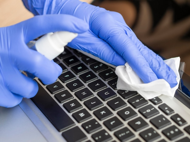 High angle of hands with surgical gloves cleansing keyboard