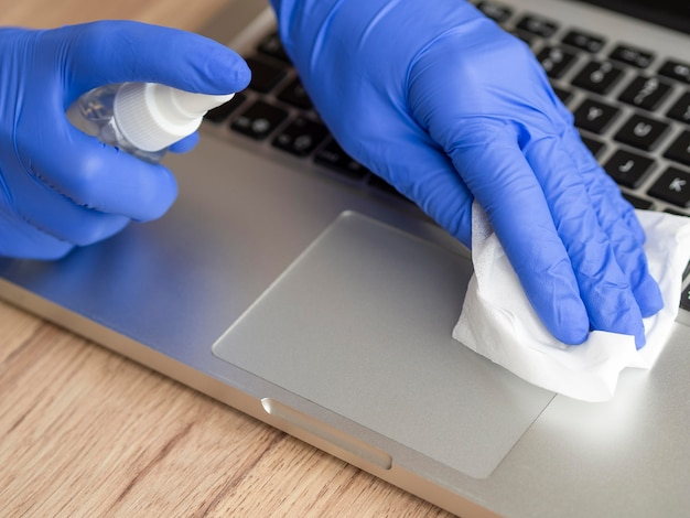 High angle of hands with surgical gloves disinfecting laptop surface