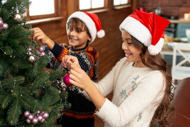 High angle happy children decorating the christmas tree