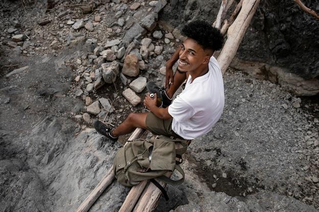 Счастливый человек, сидящий на бревнах