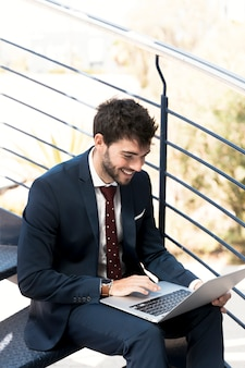High angle happy man on stairs with laptop