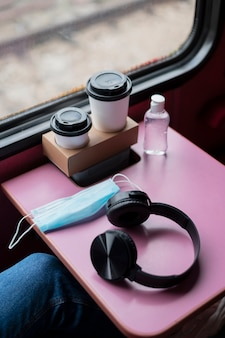 Alto angolo di cuffie e maschera medica sul tavolo del treno