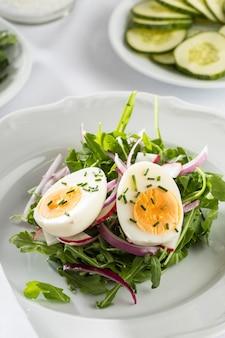 Здоровый салат под высоким углом с яйцом на белой тарелке