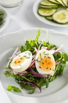 High angle healthy salad with egg on a white plate