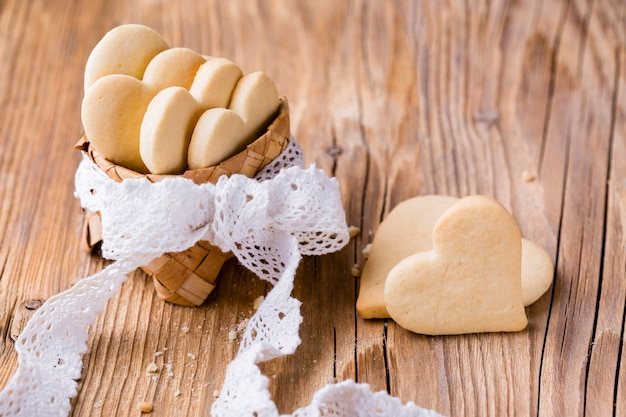 High angle of heart-shaped cookies in basket with bow